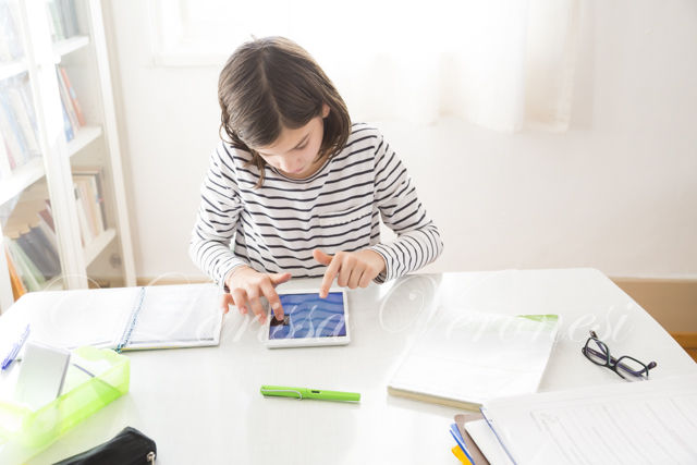 Mädchen macht Hausaufgaben mit Tablet
