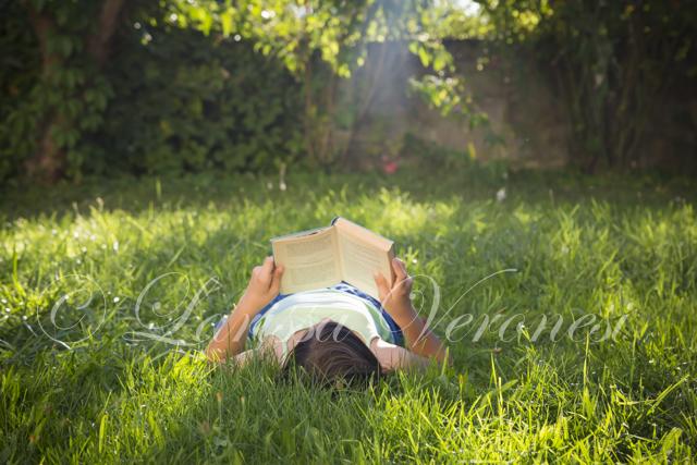 Mädchen liest auf auf Wiese