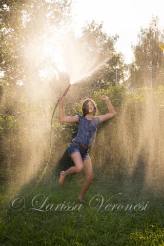 Mädchen tanzt mit Wasserschlauch