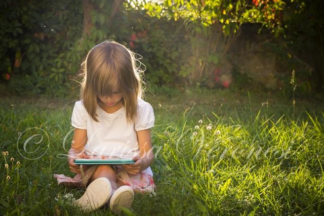 Mädchen mit Tablet im Garten