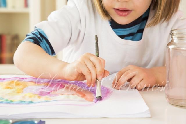 kleines Mädchen malt mit Wasserfarben