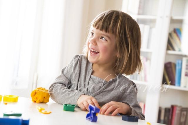 kleines Mädchen spielt mit Knete