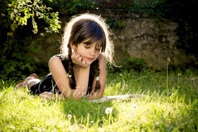 Mädchen liest ein Buch auf einer Wiese