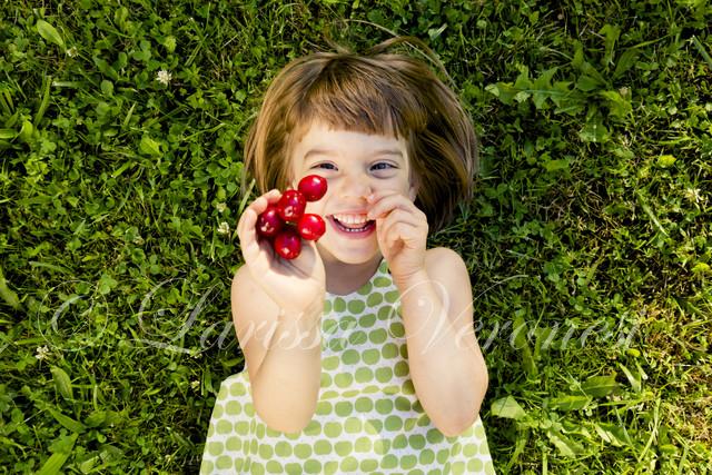 kleines Mädchen mit Kirschen