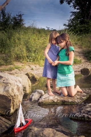 zwei Mädchen mit Holzspielboot