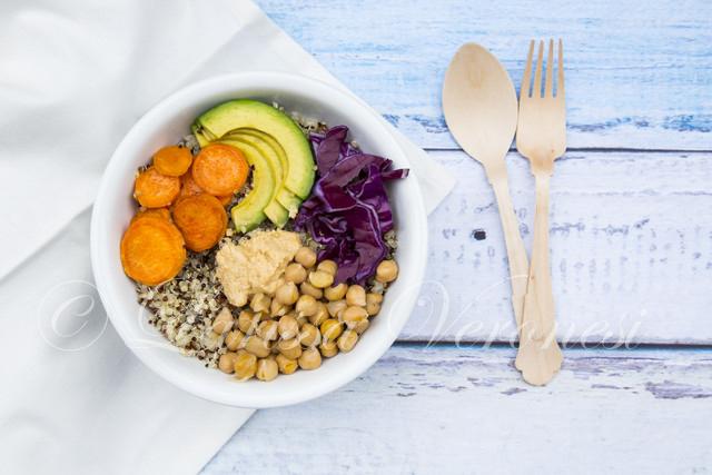 Lunch bowl mit dreifarbigen Quinoa, Avocado, Rotkohl, Karotten, Kichererbsen und Humus