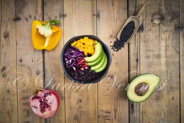 Lunchbowl mit schwarzem Reis, Avocado, gelber Paprika, Rotkohl und Granatapfelkernen
