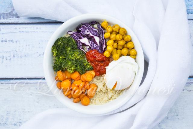 Lunchbowl mit Quinoa, pochiertem Ei, Karotten, Brokkoli, Rotkohl, gerösteten Kichererbsen und Ajvar