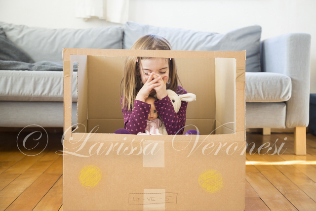 kleines Mädchen mit Pappkarton-Auto
