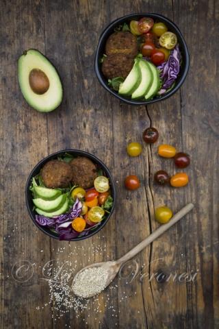 Lunch bowl mit Avocado, Quinoa-Bratlingen, Tomaten und Rotkohl